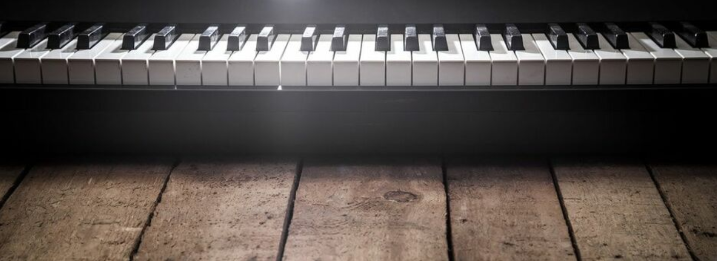 Picture of the keyboard of a piano resting on old wooden boards