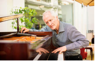 Picture of an elderly piano technician tuning a grand piano