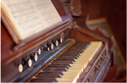 Picture of an old piano with sheet music, open and ready to play