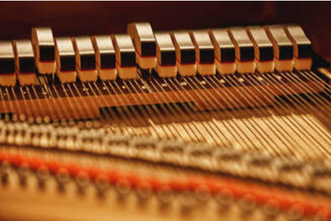 Picture of the internal mechanisms of a piano showing the strings and hammers