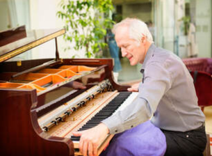 Picture of an elderly piano technician removing the keyboard of a grand piano ready to make repairs