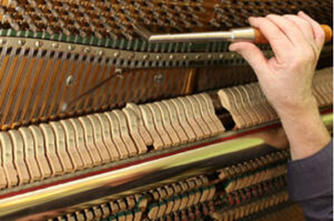 Picture of a man's hand tuning an old piano