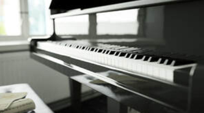 Picture of a polished piano sat ready to be played