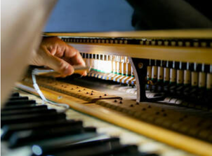 Picture of a technician repairing the mechanisms of a piano using a torch for extra light