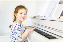 Picture of a smiling young girl sat ready to play a white upright piano